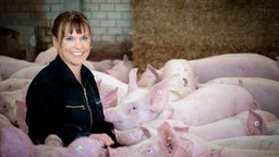 Gabriele Mörixmann zwischen Schweinen in ihrem Stall. © NDR