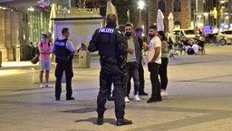 Zwei Polizisten stehen vor dem Bahnhof in Hannover vor zwei Männern mit Migrationshintergrund. © NDR Foto: Screenshot