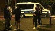 Polizisten stehen vor mit einem Einsatzwagen neben einer Gruppe Jugendlicher. © NDR Foto: Screenshot
