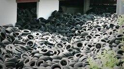 Tausende von Reifen liegen auf einem Haufen neben einem weißen Gebäude. © NDR Foto: Screenshot