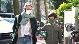 Mutter und Kind mit Atemschutzmasken