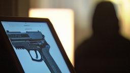 Schusswaffe der Firma Sig Sauer, im Hintergrund ein verdeckter Informant. © NDR