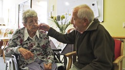 Ein alter Mann streichelt einer alten Frau die Wange © NDR Foto: Screenshot