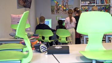 Kinder stehen vor Computern, im Vordergrund aufgestellte grüne Stühle in einem Klassenzimmer © NDR Foto: Screenshot