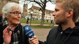 NDR Reporter Christian Deker befragt eine ältere Frau in Stuttgart. © NDR