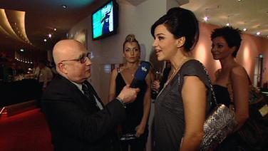 NDR Reporter Christoph Lütgert im Gespräch mit Verena Pooth, die für KiK wirbt.