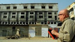 Christoph Lütgert vor der ausgebrannten Textilfabrik in Karachi.