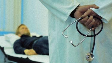 Ein Mann auf einer Liege, im Vordergrund steht ein Arzt im Kittel. © Katja Reise
