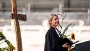Die Pastorin der Emmaus-Kirchengemeinde, Teelke Bercht, predigt vor der Tribüne des Kieler Holsteinstadions während einer Konfirmationsfeier. © dpa-Bildfunk Foto: Axel Heimken
