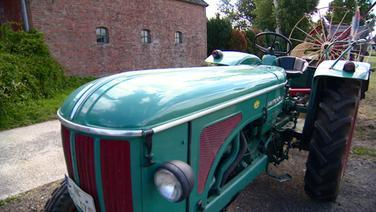 Ein alter Traktor mit landwirtschaftlicher Maschine. © NDR