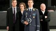 """""""Schuldig"""" oder """"nicht schuldig""""? Eurofighter-Pilot Lars Koch (Florian David Fitz, vorne) muss sich für den Abschuss eines entführten Passagierflugzeuges verantworten. Sein Verteidiger (Lars Eidinger, li.), die Staatsanwältin (Martina Gedeck) und der Richter (Burghart Klaußner, re.) in der Verhandlung. © NDR/ARD Degeto/Moovie GmbH/Julia Terjung, honorarfrei"""