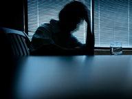 Eine Person sitzt mit auf den Händen gestüztem Kopf in einem dunklen Raum am Tisch. © DNY59 / iStockphoto Fotograf: DNY59