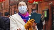 Une femme asiatique porte un masque facial. © Photoshot