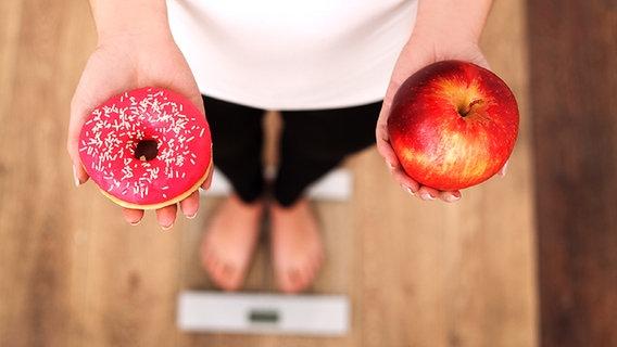 Frau steht auf einer Waage und hält einen Doughnut und einen Apfel in den Händen © Fotolia.com Fotograf: Maksymiv Iurii