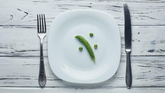 drei Ebsen und eine Ebsenschote liegen auf einem sonst leeren Teller mit Messer und Gabel. © fotolia Fotograf: alexmishchenko