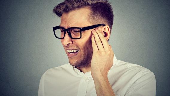 Mann hält sich das Ohr vor Schmerzen. © fotolia Fotograf: pathdoc
