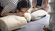 Frauen üben an eine Puppe Wiederbelebungsmaßnahmen. © fotolia.com Foto: Rawpixel