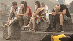 Menschen in Moskau schützen sich mit Atemnschutzmasken gegen den giftigen Qualm, den die Waldbrände verursachen (07.08.2010) © picture alliance / dpa Foto: Sergei Chirikov
