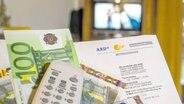 Euro-Scheine und eine Fernbedienung liegen auf einem Brief des Beitragsservices.  Fotograf: imago stock&people