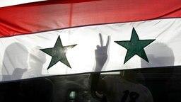 Hinter einer syrischen Fahne machen Protestler das Victory-Zeichen © picture alliance / landov