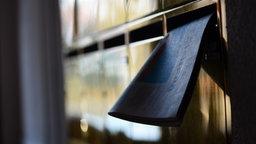 Eine Zeitung steckt halb in einem Briefkasten. © picture alliance/dpa Foto: Jens Kalaene