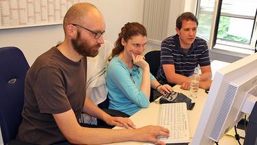 Ein Mann mit Vollbart, eine Frau mit langen rotbraunen Haaren und ein braunhaariger Mann sitzen nebeneinander in einem Büro an einem PC.  Foto: Martin Ovelgönne, NDR