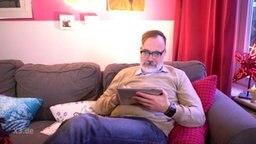 Ein Mann auf dem Sofa mit Tablet in der Hand.