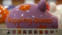 """Ein Sparschwein mit der Aufschrift: """"Shopping-Queen""""."""
