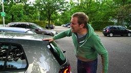 Ein Mann motzt ein Auto an.