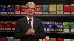 Heinz Strunk vor Zigarettenregal.
