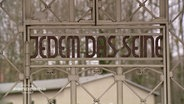 """Ein Tor mit dem Spruch: """"Jedem das Seine"""" über dem Eingang zum Konzentrationslager Buchenwald."""