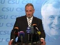Torsten Sträter am Rednerpult mit Mikrofonen vor sich, im Hintergund ein Bild Horst Seehofers.