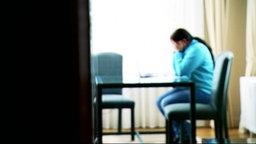 Eine Frau Sitzt Am Tisch, Hält Sich Die Hände Vor Das Gesicht.