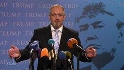 """Ein Mann spricht in mehrere Mikrophone, im Hintergrund mehrfach der Schriftzug: """"Trump""""."""