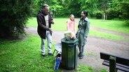 Eine Familie stellt ihren Müll an einem Mülleimer ab.
