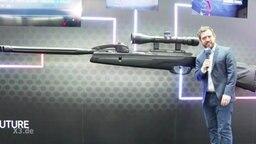 Ein kleiner Mann steht neben einer riesigen Waffe.