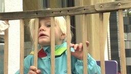 Ein Kind blickt durch einen Holzzaun.
