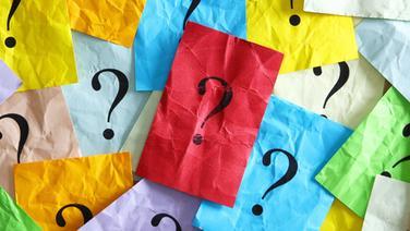 Bunte, zerknickte Zettel mit aufgedruckten Fragezeichen. © fotolia.com Foto: Stauke