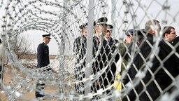 Griechische und europäische Frontex-Verantwortliche stehen hinter einem Grenzzaun. © dpa picture alliance Foto: Nikos Arvanitidis