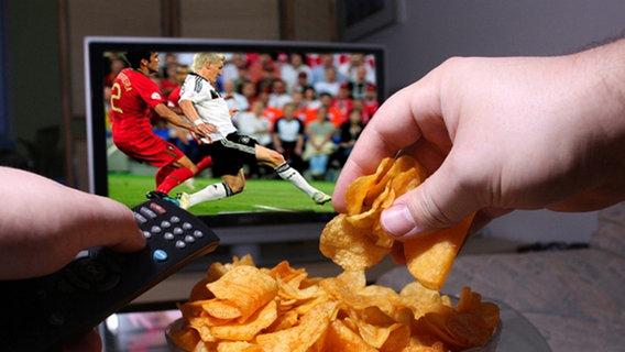 Jemand greift vor dem Fernseher in eine Chipsschüssel. Im Fernsehen läuft Fußball. © © Fabian Rothe - Fotolia.com Foto: © Fabian Rothe