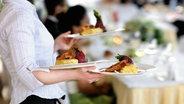 Eine Kellnerin mit drei Tellern geht durch ein Lokal. © fotolia.com Foto: MNStudio