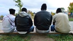 Vier junge Männer aus Eritrea sitzen in Saalfeld (Thüringen) vor einer Flüchtlingsunterkunft. © picture alliance/dpa Foto: Martin Schutt