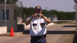 Ein Sicherheitsmitarbeiter vor dem Dagger-Komplex hält eine Fotokamera hoch. © NDR