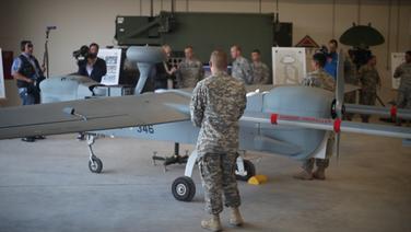 Ein Soldat in Uniform steht vor einer Drohne. Im Hintergrund filmt ein Kamera-Team. © NDR