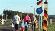 Eine Familie überquert im November 1989 mit Einkaufstüten einen geöffneten Grenzübergang zwischen DDR und BRD. © dpa - Bildarchiv Foto: Wolfgang Weihs