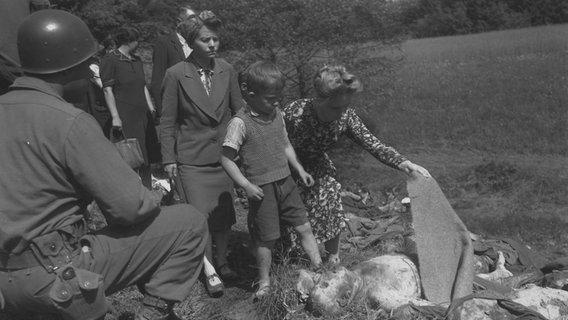 Deutsche Zivilisten, unter ihnen Kinder, müssen sich nach dem Kriegsende die Leichen von Gefangenen aus einem Massengrab anschauen. © National Archives and Records Administration, College Park