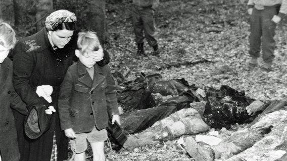Eine deutsche Mutter schirmt die Augen ihres Sohnes ab, während sie mit anderen Zivilisten an Leichen vorbeigeht, die nach dem Zweiten Weltkrieg aus einem Massengrab exhumiert wurden. © National Archives and Records Administration, College Park