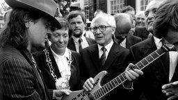 """SED-Generalsekretär Erich Honecker erhält 1987 in Wuppertal von Udo Lindenberg eine Gitarre mit der Aufschrift: """"Gitarren statt Knarren"""". © dpa/ Picture-Alliance Foto: Franz-Peter Tschauner"""