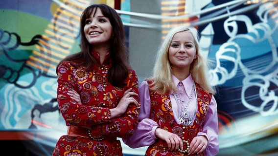 Fashion in the GDR 1970: Two models present a trouser suit with tunic and mini skirt with vest and blouse from VVB clothing.  © picture-alliance / akg-images Photo: Guenter Rubitzsch