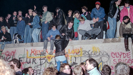 People celebrate the fall of the Berlin Wall on November 10, 1989 in front of and on top of the Berlin Wall.  © picture-alliance / ZB Photo: Peter Zimmermann
